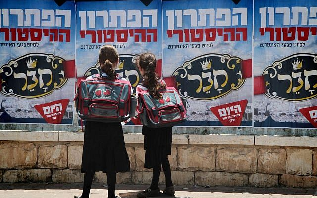 Orthodox schoolgirls looking at posters in Beit Shemesh in June 2014. (Yaakov Lederman/Flash90)