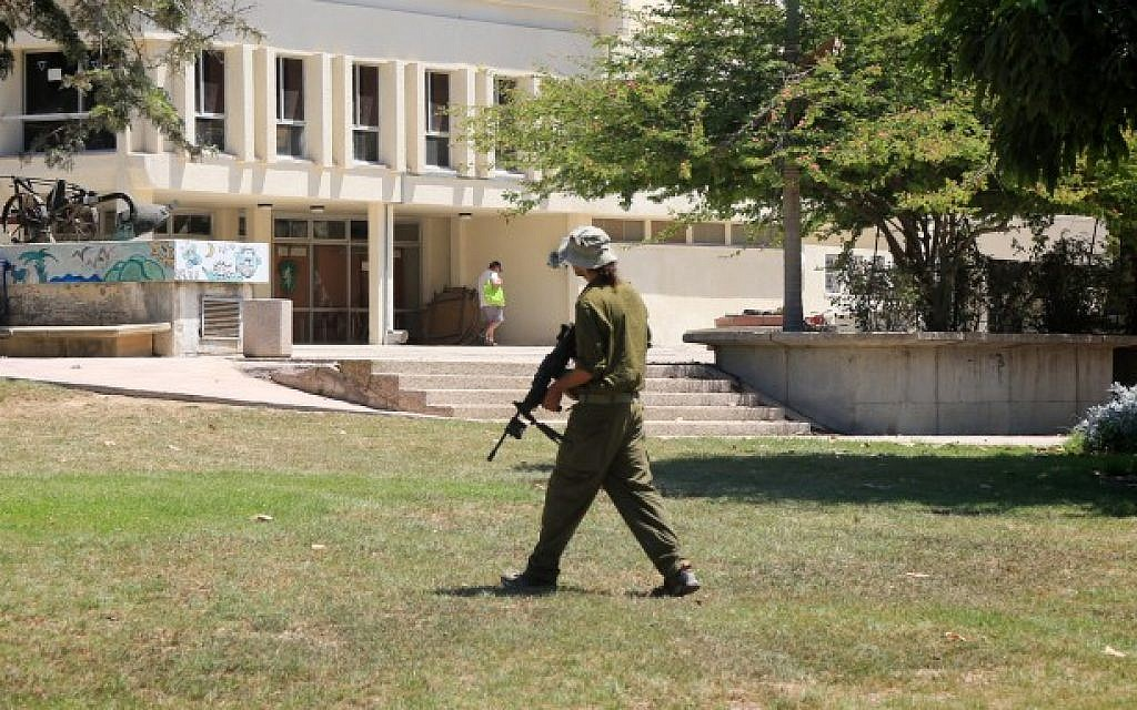 An Israeli soldier walks in Kibbutz Nahal Oz near the Gaza border after it was temporarily abandoned by residents after it was targeted by volleys of rockets from the Gaza Strip during Operation Protective Edge, summer 2014. (Edi Israel/Flash90)