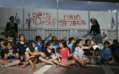 "School children wave the Israeli flag as they sit in their school playground in front of a dividing barrier put up by the Beit Shemesh municipality, September 02, 2014. Graffiti  reads ""Separation barrier, a disgrace to Zionism"" . (photo credit: Nati Shohat/Flash90)"