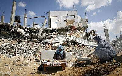 Palestinian women bake bread amid the rubble of their destroyed home in the town of Khan Younis, southern Gaza Strip, September 21, 2014. (Abed Rahim Khatib/Flash90)