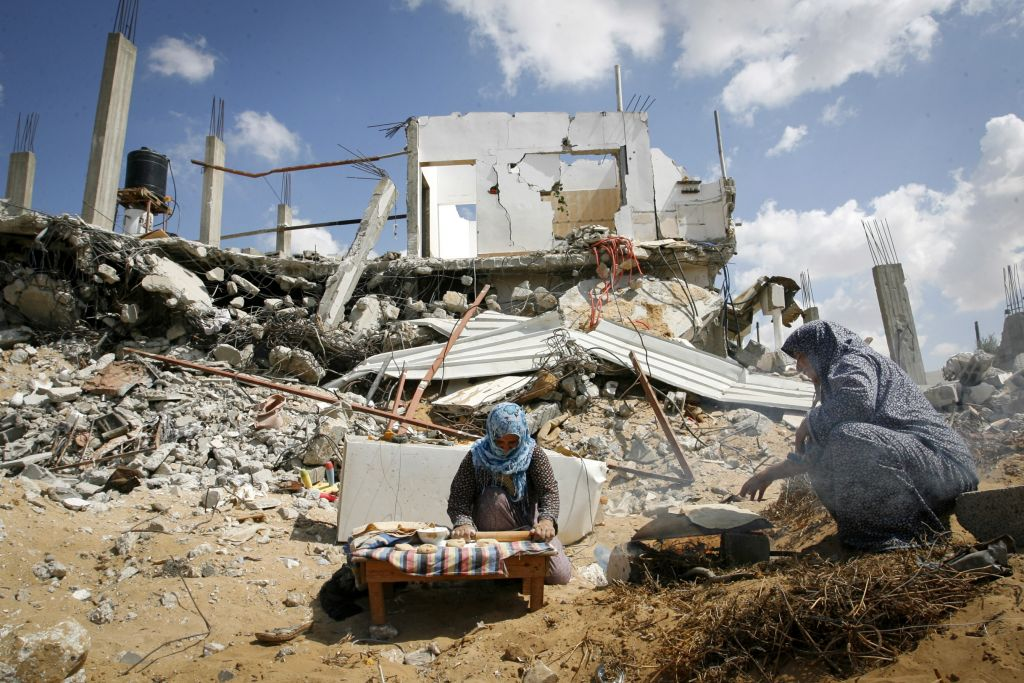 Palestinian women bake bread as they prepare lunch amid the rubble of their destroyed home in the town of Khan Younis, southern Gaza Strip, September 21, 2014 (photo credit: Abed Rahim Khatib/Flash90)