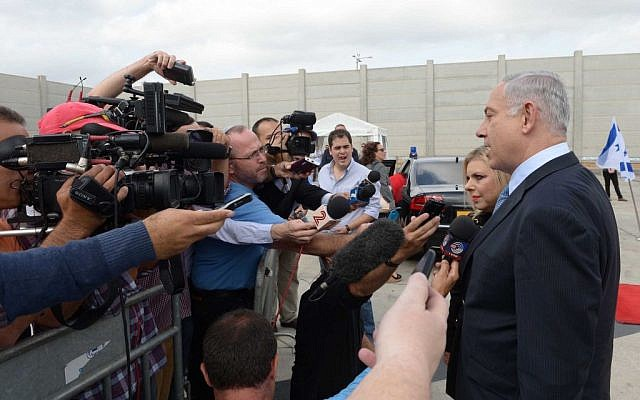 Prime Minister Benjamin Netanyahu and his wife, Sara Netanyahu, speak with Israel media at the Ben Gurion Airport, Tel Aviv, before they depart for the United States on Sunday, September 28, 2014. (Avi Ohayon/GPO/Flash90)