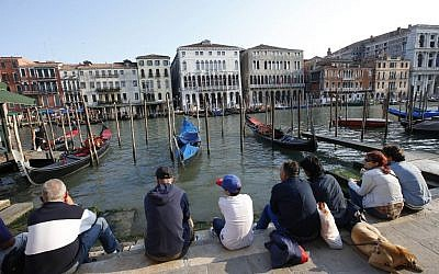People sitting by the Grand Canal in Venice, Italy, on Thursday, September 25, 2014. (AP/Luca Bruno)