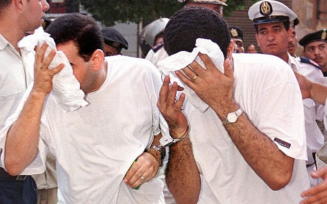 Two of 52 men accused of breaking laws covering obscenity and public morality cover their faces as they enter a state security court for their trial, in Cairo, Egypt on July 18, 2001. (photo credit: AP Photo/ File)