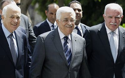 PA President Mahmoud Abbas (center), arrives with the Arab League's Secretary-General Nabil Elaraby (left), and Palestinian Foreign Minister Riyad al-Maliki (right) to attend a meeting of Arab foreign ministers at the Arab League headquarters in Cairo, Egypt, on Sunday, September 7, 2014. (photo credit: AP/Hassan Ammar)