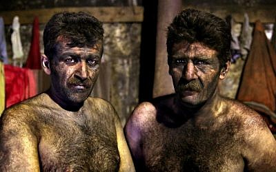 In this Wednesday, May 7, 2014 photo, Iranian coal miners pose for a photograph before taking a shower after a long day of work  more than minimum wage.(Photo credit: AP/Ebrahim Noroozi)