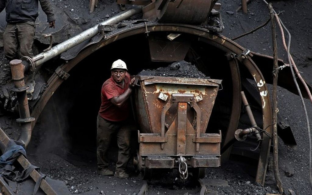 In this Monday, Aug. 18, 2014 photo, an Iranian coal miner pushes a metal cart loaded with coal.(Photo credit: AP/Ebrahim Noroozi)