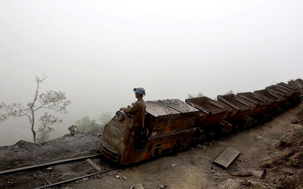 In this Thursday, May 8, 2014 photo, an Iranian coal miner moves wagons to be loaded with coal.(Photo credit: AP/Ebrahim Noroozi)