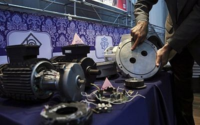 In this Monday, Sept. 1, 2014 photo, an Iranian nuclear technician shows a part of a machine of the country's nuclear facilities that Iran says was exported to the country with the alleged purpose of sabotage. (AP Photo/Vahid Salemi)