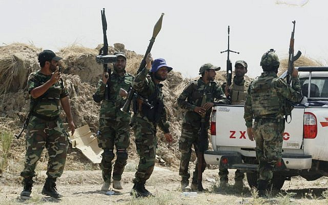 Iraqi security forces and Shiite militiamen stand guard in Amirli, some 105 miles (170 kilometers) north of Baghdad, Iraq, on Sunday, August 31, 2014 (photo credit: AP)