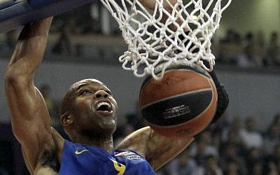 In this Thursday, March 20, 2014 file photo, Alex Tyus of Israel's BC Maccabi Electra dunks a ball during their Euroleague Top 16 basketball match against Partizan, in Belgrade, Serbia, Thursday, March 20, 2014. With his Maccabi Tel Aviv team set to face LeBron James in his first game back for the Cleveland Cavaliers on Oct. 5, 2014, Alex Tyus, a 6-9 power forward from St. Louis, has an important decision to make -- whether to fast the previous day for the Jewish holy day of Yom Kippur. American Jews have long found a basketball refuge in Israel but the Jewish state has never seen anything like Tyus before: an African-American standout from a major college program with no previous link to the religion who decided, along with his future wife, to embrace the faith and set off on a path that led him to the Israel national team and the best team in the country. (photo credit: AP Photo/Darko Vojinovic, File)