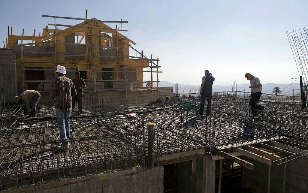 File: Palestinian laborers working at a construction site in the West Bank settlement of Ma'ale Adumim, near Jerusalem, September 16, 2014. (photo credit: AP/Dan Balilty)