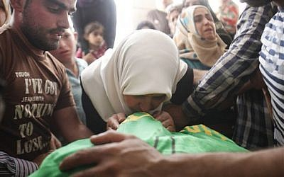 The mother of Amer Abu Aysha kisses the lifeless body of her son after Israeli troops shot dead Abu Aysha and Marwan Qawasmeh in the West Bank city of Hebron, on Tuesday, September 23, 2014. (photo credit: AP/Nasser Shiyukhi)