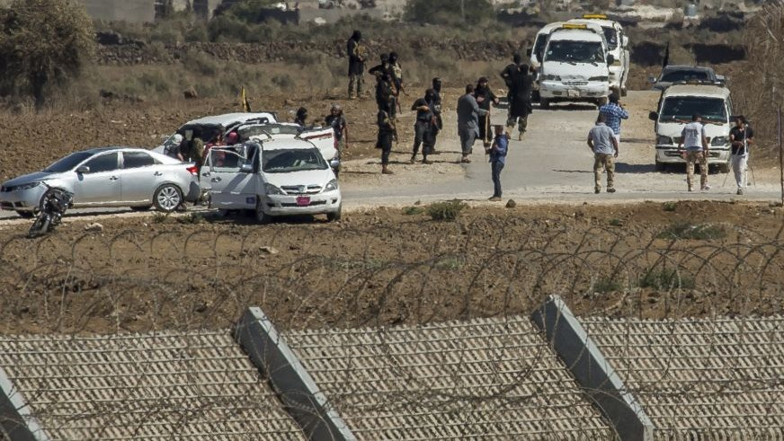 Al-Qaida-linked Syrian militants gather around vehicles carrying U.N. peacekeepers from Fiji before releasing them, as they arrive near the Syrian village of Al Rafeed in Syrian-controlled side of the Golan Heights, seen from the border of the Israeli side Thursday, Sept. 11, 2014. Al-Qaida-linked Syrian militants on Thursday released all 45 Fijian peacekeepers they had held captive for two weeks, the United Nations said, bringing an end to a crisis that ensnared the U.N. monitoring force in the chaos of Syria's civil war. (photo credit: AP Photo/Gil Eliyahu)