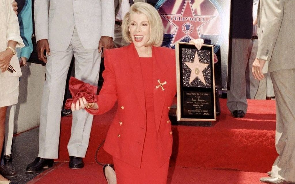 Joan Rivers poses next to her star on the Hollywood Walk of Fame during her induction ceremony in Los Angeles,  July 26, 1989. (photo credit: AP/Doug Sheridan, File)