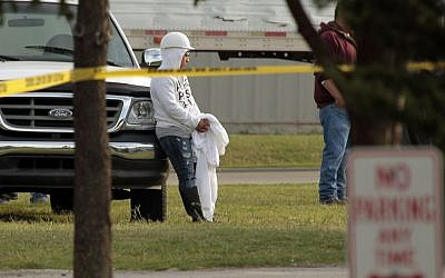 Employees wait in the parking lot as police investigate a shooting at Vaughn Foods in Moore, Oklahoma, on Thursday, September 25, 2014. Police said Friday a man who had been fired from the food-processing plant beheaded a woman with a knife and was attacking another worker when he was shot and wounded by a company official. (photo credit: AP/The Oklahoman, Steve Sisney)