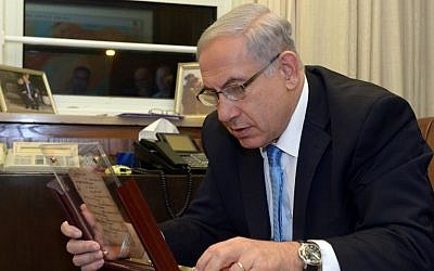 Prime Minister Benjamin Netanyahu examines what is said to be the world's oldest prayer book, now on display at the Bible Lands Museum, 2104. (photo credit: Chaim Tzach)