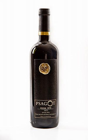 A bottle of a 2011 Psagot Edom, adorned with a copy of the ancient coin found in the cave behind Yaakov Berg's Psagot home (Courtesy Psagot Winery)