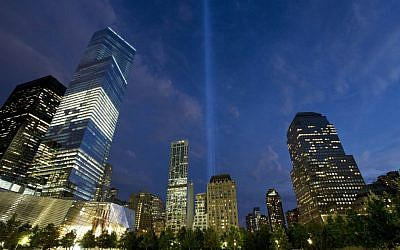 In this Monday, September 8, 2014, photo, the Tribute in Light rises behind buildings adjacent to the World Trade Center in New York. (photo credit: AP/Mark Lennihan)
