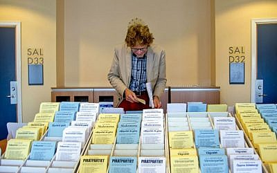 A man chooses among the ballot papers at a polling station in Goteborg during the Swedish general elections Sunday, Sept. 14, 2014. (photo credit: AP/Adam Ihse)