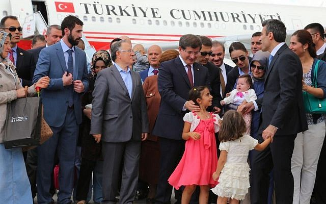 Turkish Prime Minister Ahmet Davutoglu, center right, stands with freed hostages at the airport in Ankara, Turkey, Saturday, Sept. 20, 2014. (Photo credit: AP)