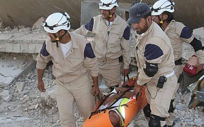 In this photo posted on August 21, 2014, Syrian civil defense rescuers in white helmets carry one of their comrades during a training session, in Idlib province, northern Syria. (AP/Civil Defense Idlib)