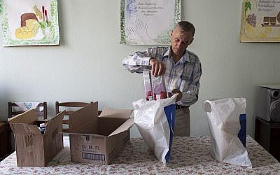 JDC volunteer Vladimir packing bags of food intended for clients. Vladimir, who isn't Jewish, remained in Slavyansk helping JDC clients throughout the fighting. He delivered food to clients in small bags to reduce detectability and possible confiscation. (JDC, August 2014)