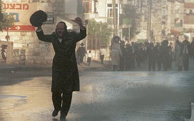 Illustrative photo of an ultra-Orthodox man yelling as he walks in Mea Shearim where police were breaking up a protest using water canon. The protest, in August 1996, was by local ultra-Orthodox residents seeking to close a main road in the area to traffic on Shabbat. (Photo credit: Nati Shohat Flash90)