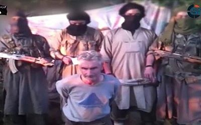 In this still image from a video published on the Internet on Wednesday, September 24, 2014, by a group calling itself Jund al-Khilafah, or Soldiers of the Caliphate, members of the group stand behind French mountaineer Herve Gourdel just before beheading him. (photo credit: AP)