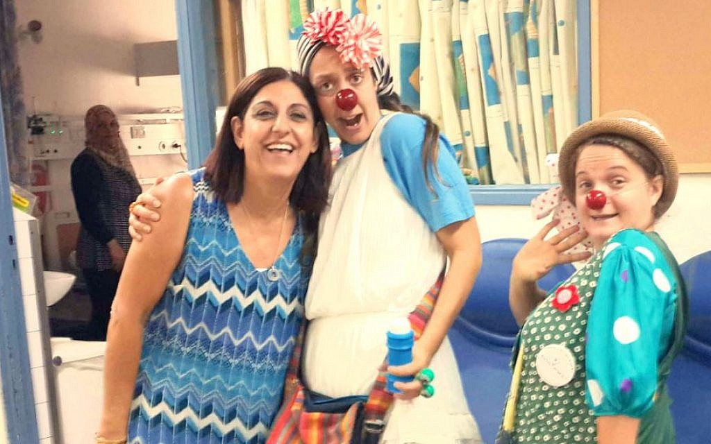 Ilana Levy, left, with two medical clowns doing their rounds in the pediatric unit. (photo credit: Debra Kamin/Times of Israel)