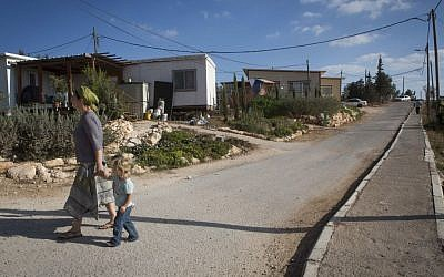 A woman seen walking with young children in the streets of the settlement of G'vaot on September 2, 2014. (Photo credit: Miriam Alster/FLASH90)