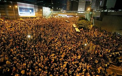 Protesters gather at a main road in the financial central district after riot police use tear gas against them after thousands of people blocked the road in Hong Kong, Sunday, Sept. 28, 2014. (AP Photo/Vincent Yu)