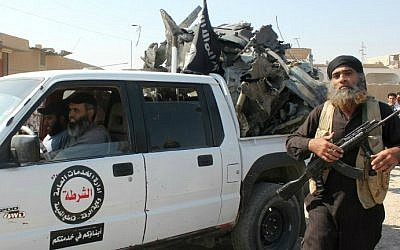 An Islamic State gunman walks past a pick up truck loaded with the wreckage of a Syrian government aircraft shot down by militants over the Syrian town of Raqqa on September 16, 2014. (photo credit: STR/AFP)