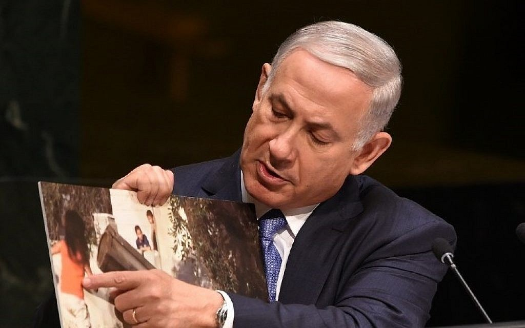 Prime Minister Benjamin Netanyahu holds up a photo of an alleged Hamas rocket near children as he addresses the 69th session of the United Nations General Assembly at the UN in New York, September 29, 2014. (photo credit: AFP/Don Emmert)