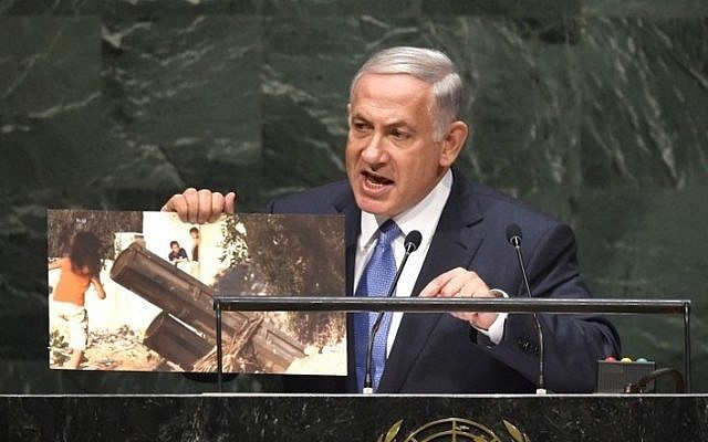Prime Minister Benjamin Netanyahu holds up a photo of a purported Hamas rocket as he addresses the 69th Session of the UN General Assembly, September 29, 2014, in New York. (photo credit: AFP/Timothy A. Clary)