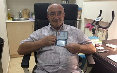 Yaakov Weksler-Waszkinel shows off his new Israeli identity card at his home in Jerusalem. (photo credit: Renee Ghert-Zand/The Times of Israel)