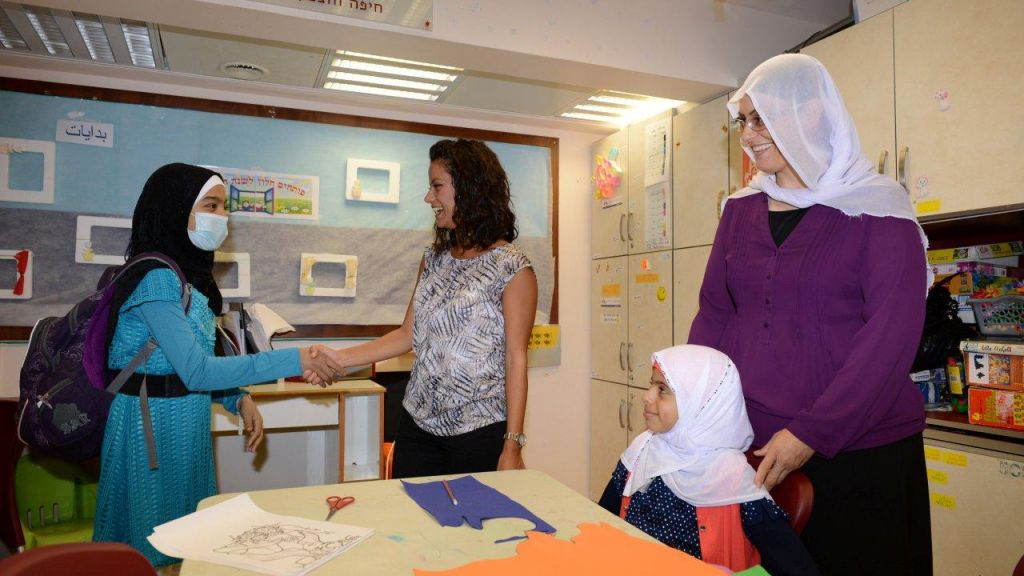 Dima Chamra, an Arab art therapist at Rambam, greets 17-year-old Sana Charoob, a patient from Jenin (left), while Amtaz Manfor, a Druze teacher at Rambam, stands behind 8-year-old patient Simdosh Chansan Jamal, also from Jenin (right). (photo credit: Ofer Golan)