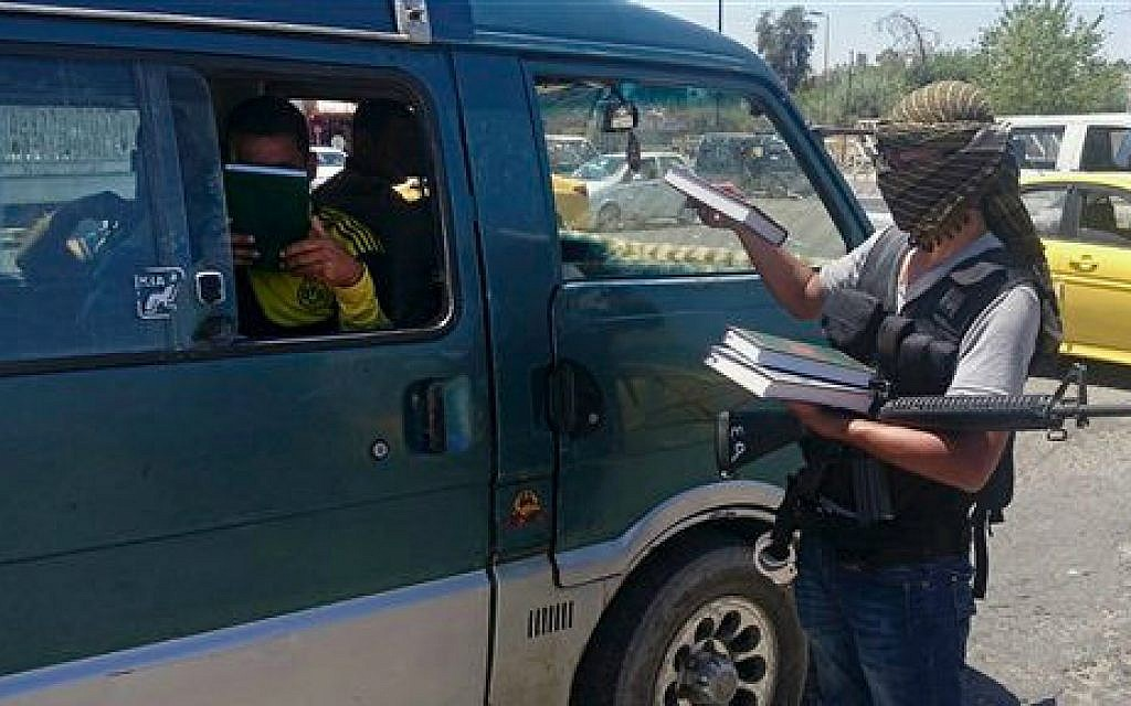 In this Sunday, June 22, 2014 file photo, a fighter from the Islamic State group, distributes a copy of the Quran to a driver in Mosul, 225 miles (360 kilometers) northwest of Baghdad, Iraq (photo credit: AP)