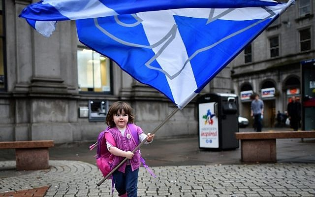 A child plays with a pro-independence 'Yes' flag on the streets of Aberdeen in Scotland, on September 15, 2014, ahead of the referendum on Scotland's independence. (photo credit: AFP PHOTO/BEN STANSALL)