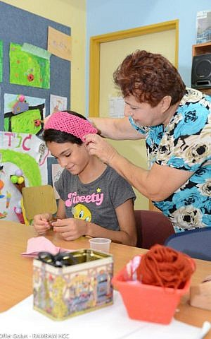 A teacher helps Amal Darauah, 10, a Christian Arab from the Israeli town of Nazareth. (photo credit: Ofer Golan)