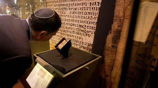 Israeli Parliament Speaker Yuli Edelstein looks at an ancient prayer book on display at the Bible Lands museum in Jerusalem, Thursday, Sept. 18, 2014 (photo credit: AP/Sebastian Scheiner)