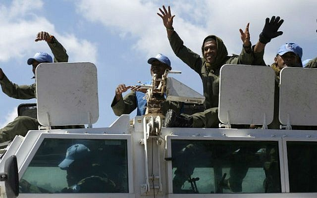 UN Fijian peacekeepers members of the United Nations Disengagement Observer Force (UNDOF) wave as they ride on top of a vehicle while leaving the Syrian side of the Golan Heights into the Israeli side of the strategic plateau, on September 15, 2014 (photo credit: AFP/ JALAA MAREY)