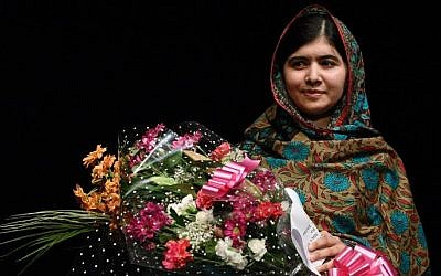 Pakistani rights activist Malala Yousufzai holds bouquets of flowers after addressing the media in Birmingham, central England on October 10, 2014. (photo credit: AFP/OLI SCARFF)