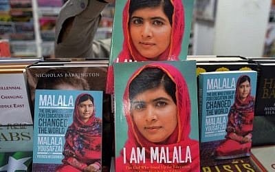 "A Pakistani customer picks up a biography of Malala Yousafzai at a bookstore in Islamabad on October 10, 2014. Malala Yousafzai was hailed as the ""pride of Pakistan"" by Prime Minister Nawaz Sharif for winning the Nobel Peace Prize, as a former fellow pupil said the award was a victory for every girl in the country. (photo credit: AFP/Aamir QURESHI)"
