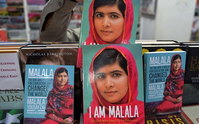 """A Pakistani customer picks up a biography of Malala Yousafzai at a bookstore in Islamabad on October 10, 2014. Malala Yousafzai was hailed as the """"pride of Pakistan"""" by Prime Minister Nawaz Sharif for winning the Nobel Peace Prize, as a former fellow pupil said the award was a victory for every girl in the country. (photo credit: AFP/Aamir QURESHI)"""
