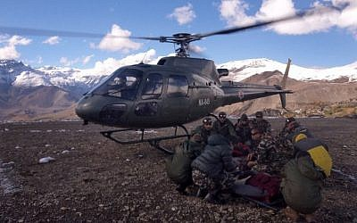 An injured survivor of a snowstorm is assisted by army personnel into a Nepalese Army helicopter in Manang District, along the Annapurna Circuit Trek, on October 15, 2014. (photo credit: AFP/Nepalese Army)