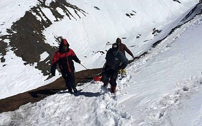 In this handout photograph released by the Nepal Army on October 17, 2014, a survivor injured in a snowstorm is carried on a stretcher by Nepal Army personnel to an army helicopter in the Manang district along the Annapurna Circuit Trek. (Photo credit: AFP/NEPAL ARMY)