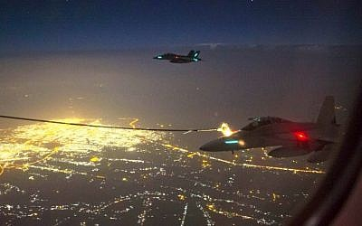 A handout photo taken October 5, 2014 and obtained on October 9 shows two Royal Australian Air Force (RAAF) F/A-18F Super Hornet aircraft refueling from a RAAF KC-30A Multi Role Tanker Transport aircraft above a city in Iraq. (AFP/Australian Defense/Sergeant Hamish Paterson)