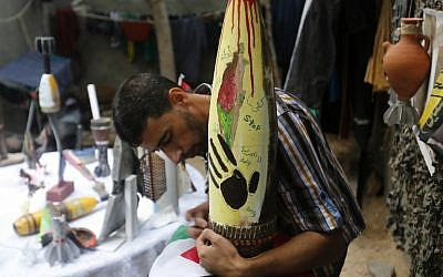 Palestinian artist Mohammed al-Zamar poses with an adorned used and diffused ammunition round on September 24, 2014, in the Bureij refugee camp in central Gaza. (photo credit: AFP Photo/Mohammed Abed)