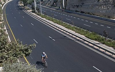 A man rides his bicycle on a car-free highway in Jerusalem during the Jewish High Holiday of Yom Kippur on October 4, 2014 (Menahem Kahana/AFP)